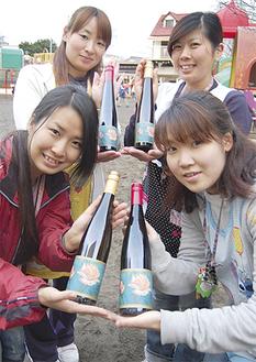地域に向けて出荷するワインを手に笑顔を見せる教諭たち
