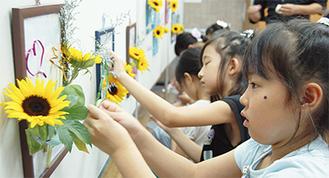 彩り鮮やかな生け花を楽しむ児童たち