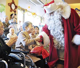 サンタクロースからプレゼントを受け取り、笑顔を見せる入居者たち