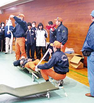 消防署員から運搬方法や応急処置を学ぶ参加者たち
