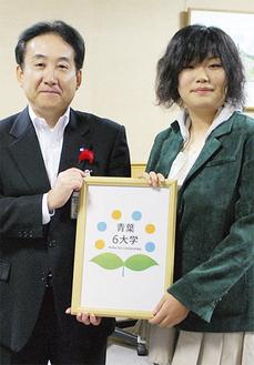 ロゴを手にする増田さんと徳江雅彦区長