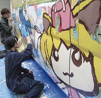 車両に絵を描く多摩美大の学生たち
