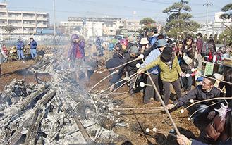 どんど焼きの余熱で団子を焼く参加者たち