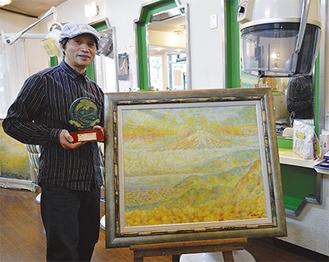 店内で盾を手にする早川さんと、受賞作品「黄金富士」