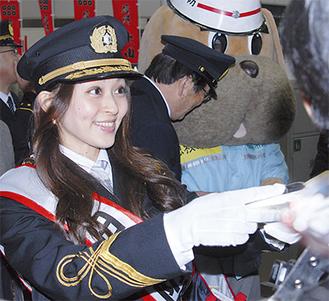 チラシを配る田中理恵さん=たまプラーザ駅前