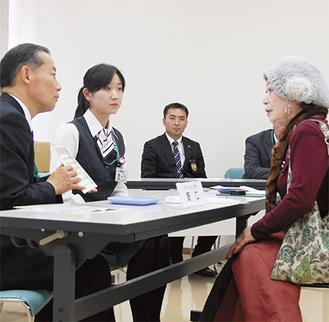 被害者役の女性(右)を説得する荏田支店の職員
