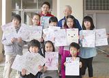 手づくりポスターを手にする児童ら。上段左は2組担任の北嶋晃吉(あきよし)教諭