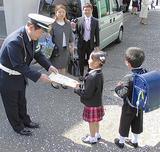 山内小でランドセルカバーを手渡す交通安全協会役員