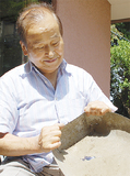 墜落したB29の破片で作ったという塵取りを手にする石原さん(86)