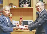 寄付金を手渡す志村さん(左)