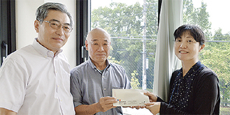 依藤会長(中央)らから作業費を受け取る古谷施設長