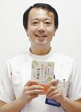書籍を手に笑顔の桜井院長