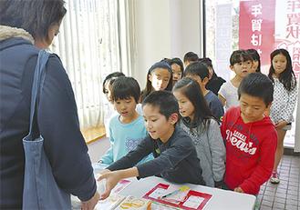 年賀状を販売する児童