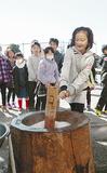 子ども用の杵で餅をつく児童