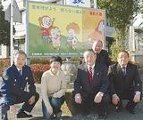 看板をデザインした飯倉さん(左から2人目)