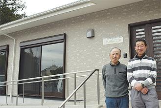 集会所の前に立つ井田会長(左)と原委員長