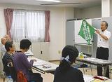 緑のバンダナを見せる佐藤さん