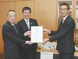 目録贈呈式。左から亀山校長、工藤代表、石坂支店長