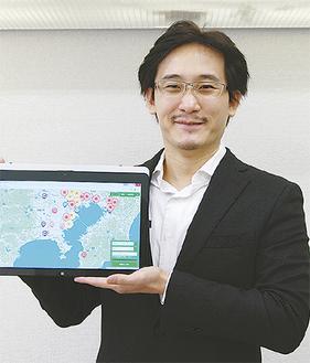 「病気予報マップ」の画面を手にする松田さん