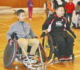 選手と車いすラグビーを体験する児童(左)