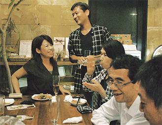 参加者と談笑する坂佐井さん(中央)