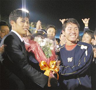 花束を受け取るスーツ姿の山崎選手(左)