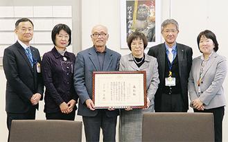 表彰状を掲げる志村会長(左から3人目)