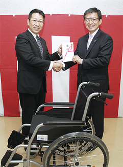 寄贈された車いすと工藤代表(右)、今村代表