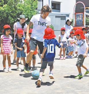 田村選手(中央)とボールを追いかける園児