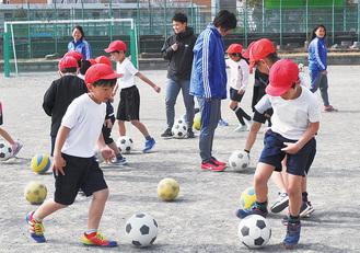 児童にボールの扱い方を教える選手たち