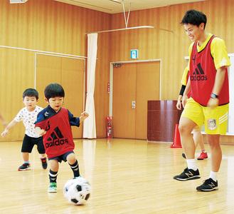 ボールを蹴る子どもと嶋田キャプテン