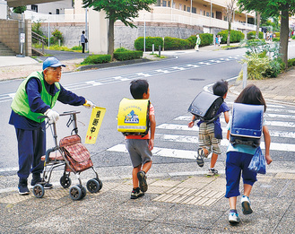 登校する児童に声をかける平野さん