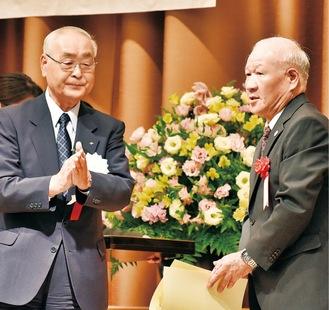 受賞者を称える市交通安全協会の板橋悟会長(左)