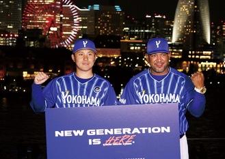 みなとみらいの夜景をバックに新スローガンを掲げる佐野選手(左)とラミレス監督