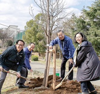 桜の植樹をするメンバー=提供