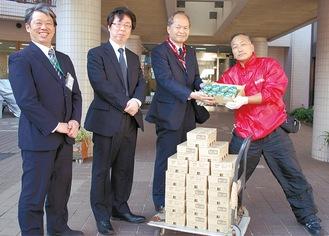 乳製品を手渡す北嶋さん(右)と緑成会の職員