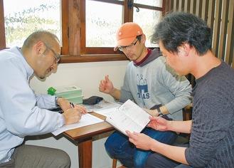 配布方法を確認する外山会長(左)と役員ら