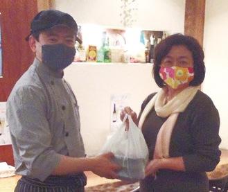 上野さん(右)に配達弁当を手渡す植木さん=提供写真