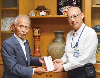 寄付金を渡す志村さん(左)
