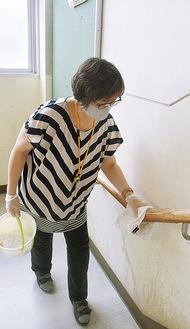階段の手すりを雑巾で消毒するPTA役員