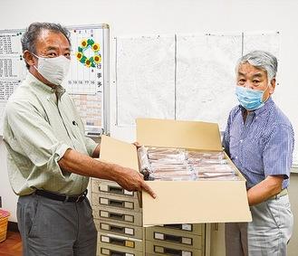 鉛筆を渡す井上会長(右)と、青木校長