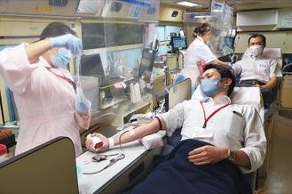 感染症対策を取った献血バス内で献血を行う様子