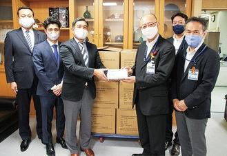 マスクを手渡す安武監督(左)と小澤区長