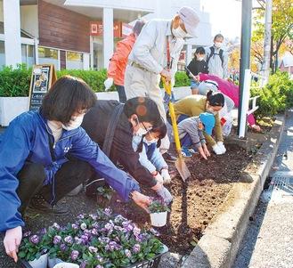 道沿いに花を植える参加者たち