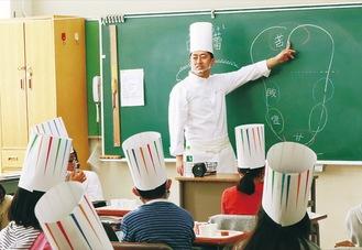 コック帽をかぶり授業を受ける児童