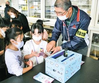 児童に手順を説明する自治会のボランティア