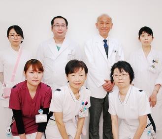 田中センター長(後列右から2番目)を中心に専門医、看護師、管理栄養士、薬剤師らがチームで治療にあたる
