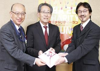 (左から)目録を贈呈する小澤区長・菊池会長と山本会長