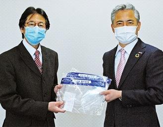 フェイスシールドを手渡す橋本代表(右)と山本会長