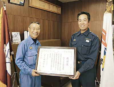 感謝状を手にする徳江団長(左)と渕上署長